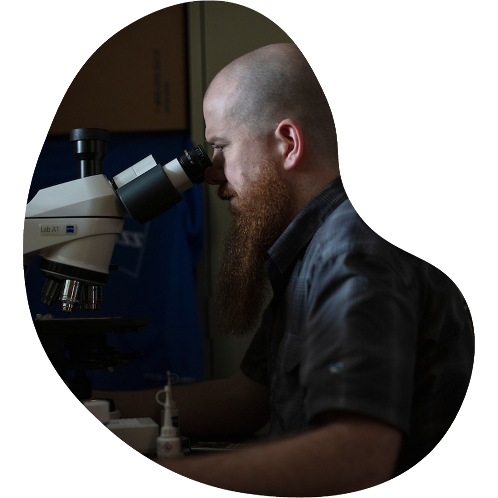 photo of bearded man behind mircoscope